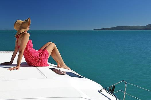 Woman relaxing on sailing boat in Whitsundays by Keiran Lusk