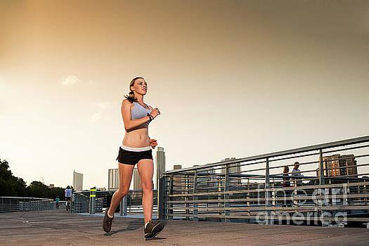 Herronstock Prints - Woman runner training for marathon on The Boardwalk Trail along Lady Bird Lake, Austin Skyline background