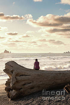 Woman Sitting on a Large Tree at Sunset on Rialto Beach in Washi by Brandon Alms