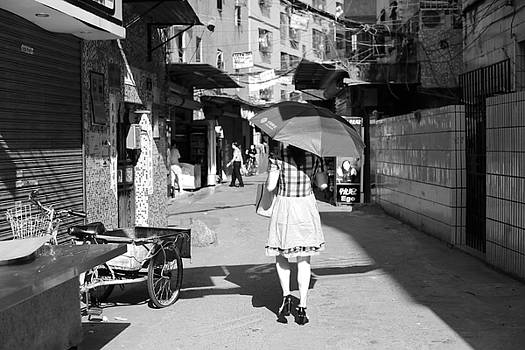 Woman walking in Shenzhen with an umbrella on a sunny day by Virginie Blanquart