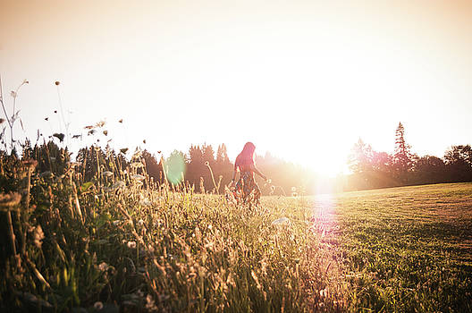 Woman walking through meadow at sunset by Bradley Hebdon