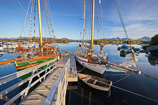 Wooden sailing ships are moored in the small boat harbor in Ringstad in Norway by Intensivelight
