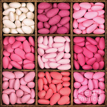 Wooden storage box filled with pink sugared almonds. by Jane Rix