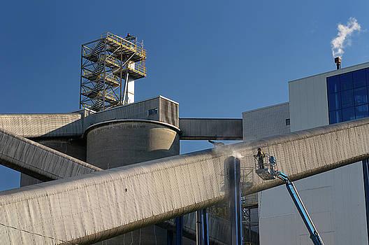 Reimar Gaertner - Worker on a boom truck lift powerwashing a outdoor conveyor chut