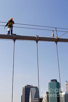 Worker on top of Brooklyn Bridge in New York City by Patricia Hofmeester
