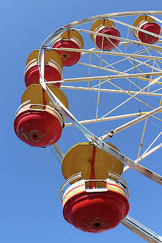 Yellow and Red Ferris Wheel Against a Blue Sky by Natalie Schorr
