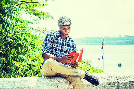 Alexander Image - Young African American Man reading red book, relaxing outdoor in New York 17061810
