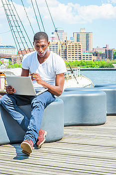 Alexander Image - Young African American Man traveling in New York, working on lap