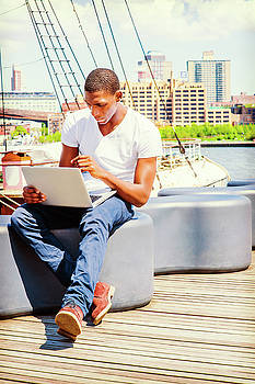 Alexander Image - Young African American Man traveling, working laptop computer in