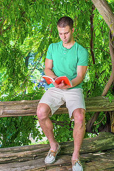 Alexander Image - Young American Man reading book, relaxing at woods in New York i