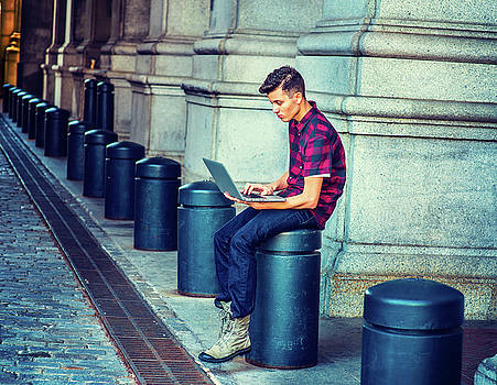 Alexander Image - Young American Man working on computer on street in New York