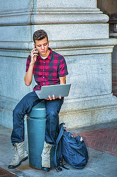 Alexander Image - Young American Man working on laptop computer, talking on cell p