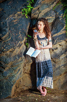 Alexander Image - Young American Woman reading book, texting on cell phone, travel