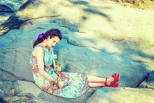 Alexander Image - Young American Woman with white rose, sitting on rocks, relaxing