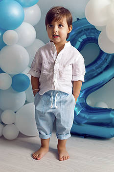 Baby Boy In Blue Pants And Shirt Standing On The Floor by Elena Saulich
