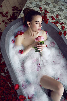 Beautiful Girl Lying In A Stone Bath With Rose Petals And Foam by Elena Saulich