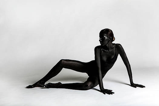 Girl Painted Black Paint Lying On A White Background by Elena Saulich