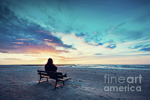 Man in hood sitting on a lonely bench on the beach by Michal Bednarek