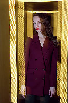 business girl in a Burgundy jacket and red shoes standing in the hallway by Elena Saulich