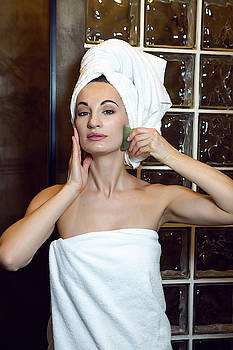 Young Girl In The Shower And In A Towel Smoothes Her Skin by Elena Saulich