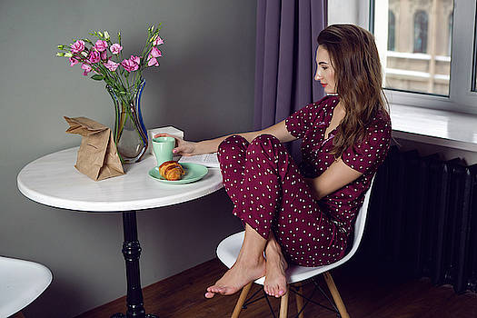 young woman in red pajamas with polka dots sitting at Breakfast by Elena Saulich
