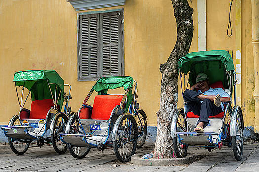 A cyclo driver takes a nap, in Hoi An, Vietnam. by Ian Robert Knight