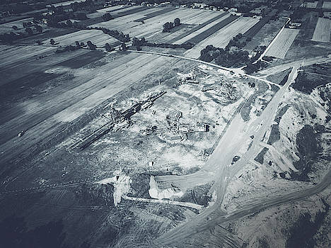 Aerial view of open pit excavator and other machinery by Lukasz Szczepanski