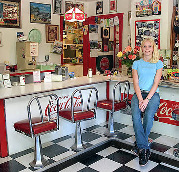 Blond teen girl in 50's American style Soda Fountain by David Smith