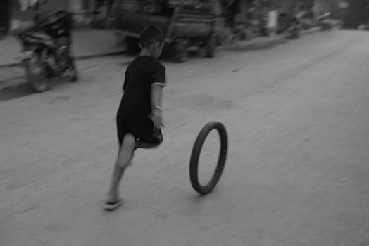 Boy Runs Tire by Timothy Leonard