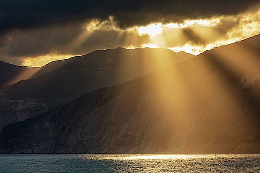 Breathtaking sunbeams between the clouds, mountain and sea by Evgeni Dinev