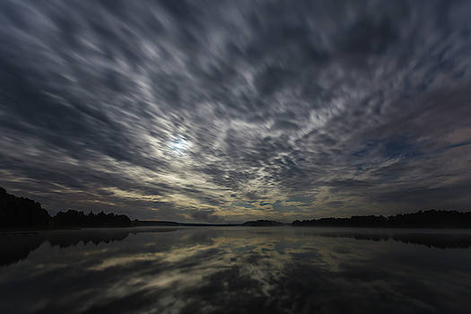 Dynamic clouds in the night over the lake lit by full moon by Lukasz Szczepanski