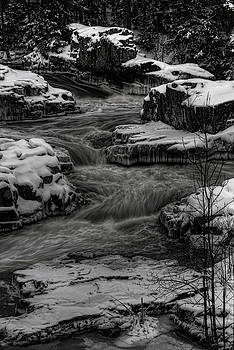 Dale Kauzlaric - Eau Claire River Through Snow Covered Rock BW