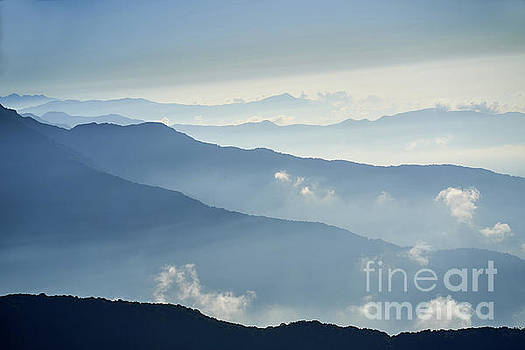 Fog above mountain in valley Himalayas mountains by Raimond Klavins