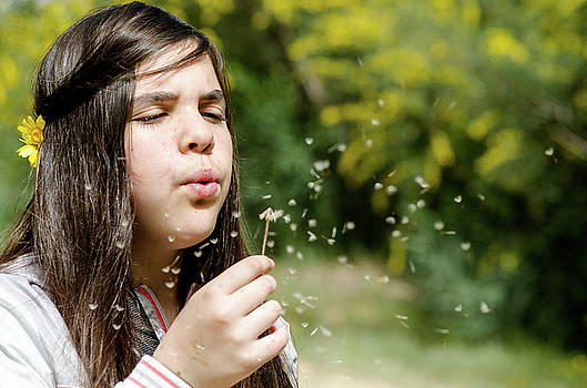Girl blowing dandelion flower by Michalakis Ppalis