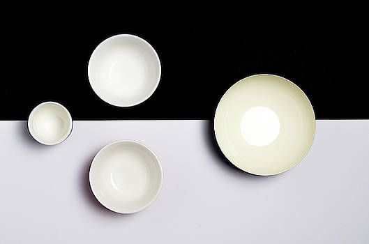 Group of empty ceramic bowls of  on a black and white surface by Michalakis Ppalis