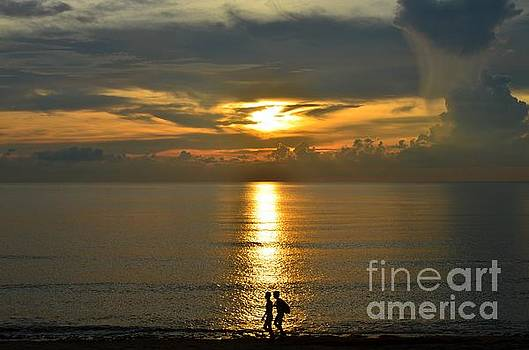 Male Swimmers walking along the sunset in photograph by Christopher Shellhammer