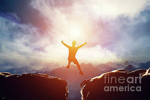 Man jumping between two mountains at sunset. by Michal Bednarek