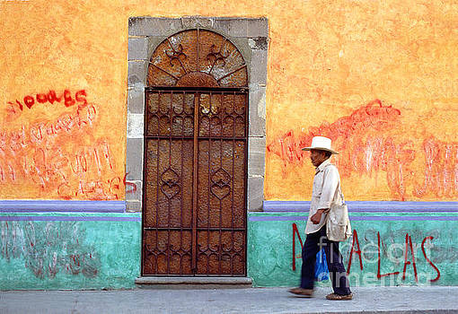 Man Walks by a Door along a colorful Wall, Morelos Mexico by Wernher Krutein