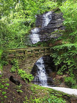 Old stone bridge over waterfall by Tatiana Travelways