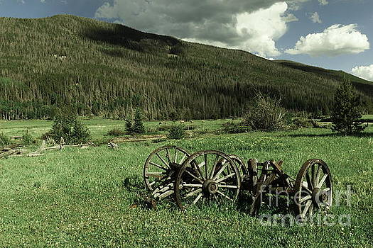 Old wagon axles and Colorado Mountains by Jeff Swan