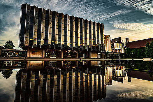 Pretty building with reflection pool near sunset by Sven Brogren
