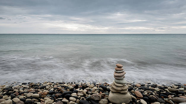 Pyramid of balancing stones , in the wavy ocean by Michalakis Ppalis