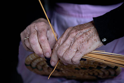 Senior woman knitting a traditional basket with reeds   by Michalakis Ppalis