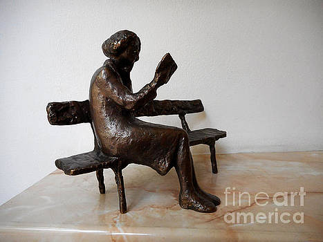 Statue of a young woman who reads a book by Nikola Litchkov