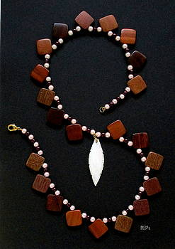 Still Life of a Necklace Made from Wood Squares, Glass Pearls and a Shell Feather by Mike Smetzer