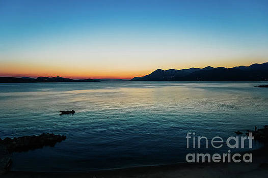 Sunset in a bay with mountains in the background and a small boa by Joaquin Corbalan