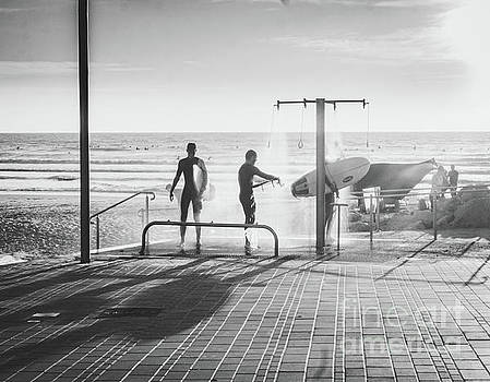 Three Surfers Rinsing off in a Beach Shower after Surfing by PorqueNo Studios