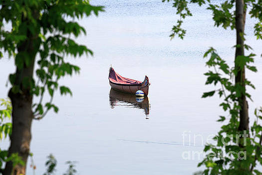 Traditional birch bark canoe on a mooring ball in Chambly Basin by Louise Heusinkveld