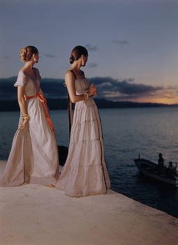Two Women In Evening Gowns By The Water At Sunset by Toni Frissell