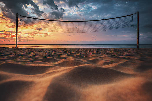 Volleyball net and sunrise on the beach  by Valentin Valkov